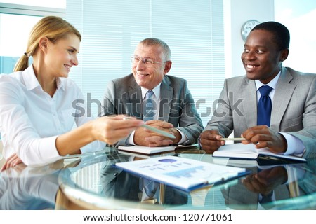 Portrait of pretty secretary pointing at paper while explaining something to her boss and colleague - stock photo
