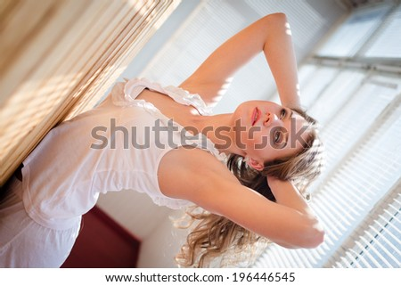 portrait of pretty, seductive young woman in pajamas looking up on balcony with shutters sun light on background - stock photo