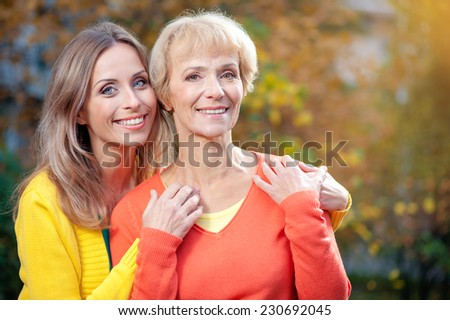 Portrait of pretty senior Mother and her adult Daughter hugging in the autumn park - stock photo