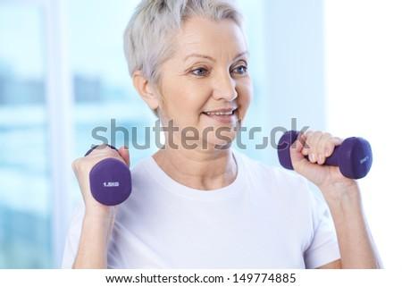 Portrait of pretty senior woman exercising with dumbbells  - stock photo