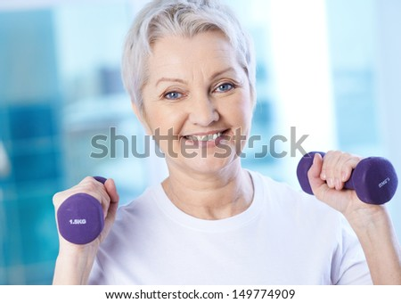 Portrait of pretty senior woman exercising with dumbbells  - stock photo