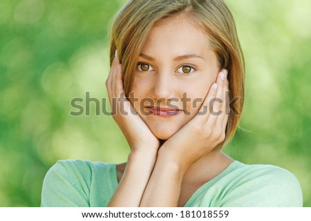 portrait of pretty, serious woman standing sideways with his arms folded, in green T-shirt, against background of summer park - stock photo
