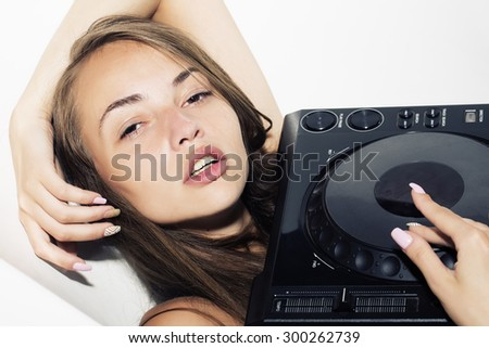 Portrait of pretty sexy young brunette dj girl with long hair lying and soft lips playing on musical mixer console with raised hand lying on white background, horizontal picture