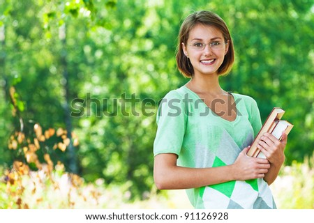 Portrait of pretty, slender student in glasses holding book against background of summer green park - stock photo