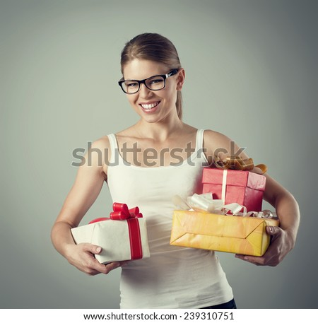 Portrait of pretty smiling Caucasian female holding colorful gift boxes. Christmas eve and holiday celebration concept. - stock photo