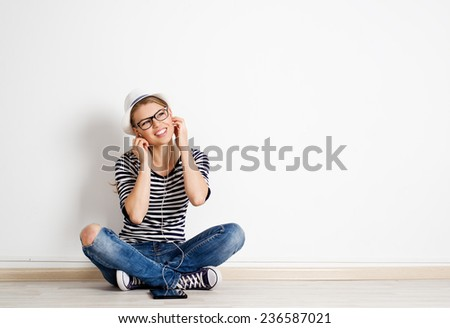 Portrait of pretty smiling girl enjoying sound from headphones. Young joyful Caucasian woman having fun at home. Student lifestyle concept.  - stock photo