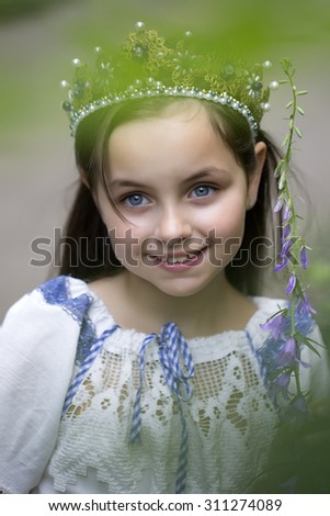 Portrait of pretty smiling princess girl with long brunette hair in traditional ukrainian embroidery white blue colors and beautiful diadem with diamonds in gold outdoor, vertical picture - stock photo