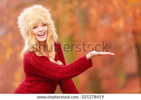 Portrait of pretty smiling woman in fall forest park with open empty palm hand for copy space. Happy gorgeous young girl in fur winter hat and sweater. Autumn fashion. - stock photo