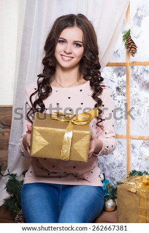 Portrait of pretty smiling woman sitting near the window with a golden gift box - stock photo