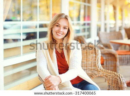 Portrait of pretty smiling young woman waiting in cafe - stock photo