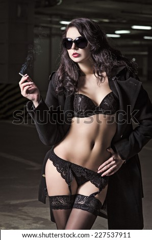 Portrait of pretty smoking young girl in black underwear and coat - stock photo