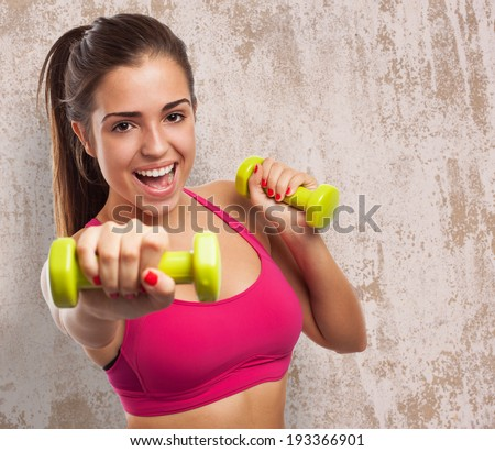 portrait of pretty sporty girl holding weights - stock photo