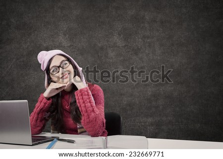 Portrait of pretty student daydream while studying in classroom and wearing warm clothes - stock photo
