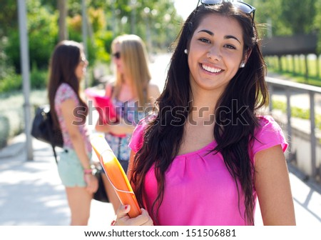 Portrait of pretty student girl with some friends at the park after school - stock photo