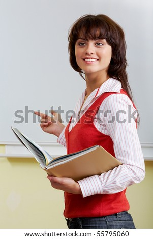 Portrait of pretty student standing at whiteboard with book in hands - stock photo