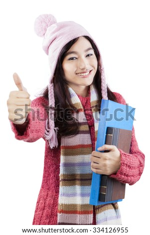 Portrait of pretty student wearing warm clothes and showing thumbs-up at the camera, isolated on white background - stock photo