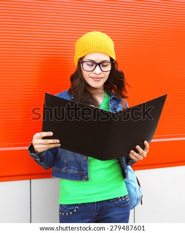 Portrait of pretty stylish student girl in glasses with folder against the colorful red wall