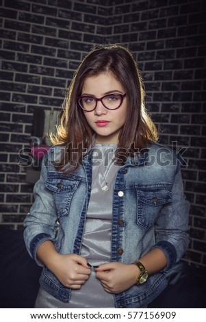 Portrait of pretty stylish teen girl wearing glasses, jeans jacket and gray dress in front of brick wall