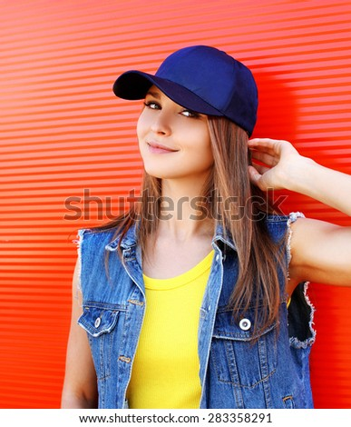Portrait of pretty stylish young girl wearing a cap and jeans clothes over red background