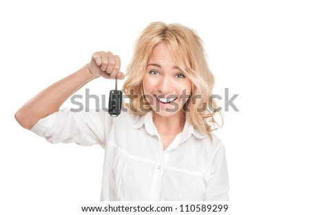 Portrait of pretty surprised young girl holding car key in her hands isolated on white background. Expression of shock, surprise and happiness. Woman got car as present or became winner. - stock photo