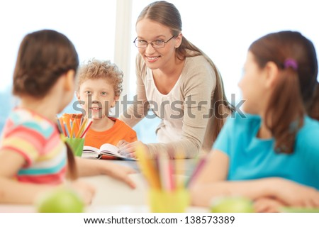Portrait of pretty teacher interacting with pupils at reading lesson - stock photo