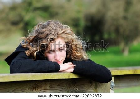 portrait of pretty teenage girl looking thoughtful - stock photo