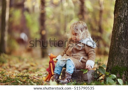 Portrait of pretty thoughtful girl in autumn park, outdoor