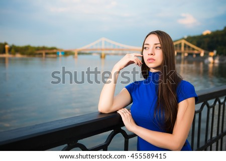 Portrait of pretty thoughtful young brunette posing near the river - stock photo