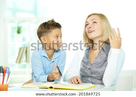 Portrait of pretty tutor sharing her idea of plot while discussing book with pupil - stock photo