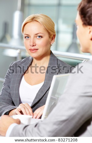 Portrait of pretty woman at workplace looking at camera