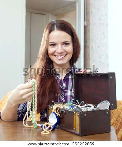 portrait of pretty woman chooses jewelry in treasure chest at home - stock photo