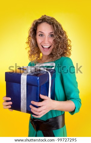 Portrait of pretty woman holding present in the blue box on a yellow background