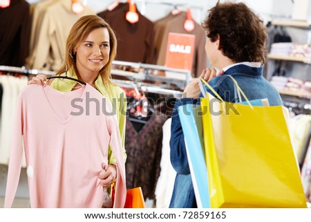 Portrait of pretty woman holding tanktop while asking her boyfriend for advice - stock photo