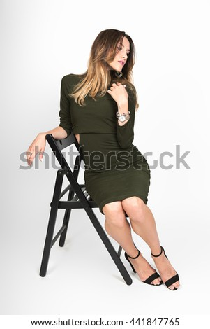 Portrait of pretty woman in green dress. Woman in green dress resting in a chair. - stock photo