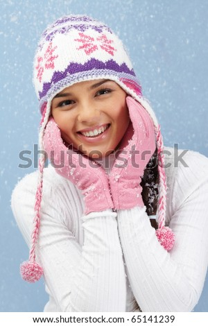 Portrait of pretty woman in pink gloves and knitted winter cap looking at camera with smile - stock photo