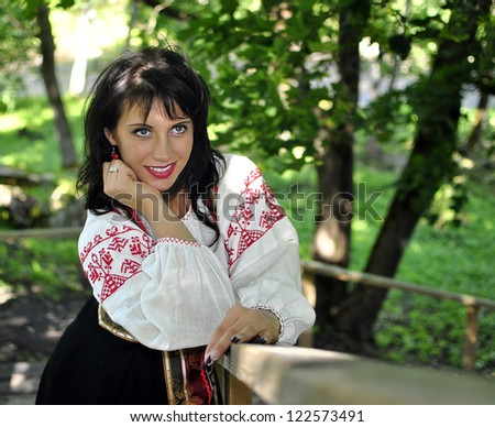 Portrait of pretty woman in russian traditional costume in the park - stock photo