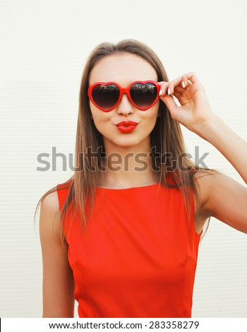 Portrait of pretty woman in the red sunglasses blowing lips having fun outdoors - stock photo