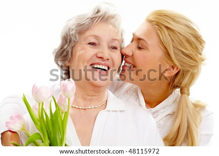 Portrait of pretty woman kissing and embracing her mother during holiday - stock photo
