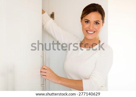 portrait of pretty woman opening a closet door  - stock photo
