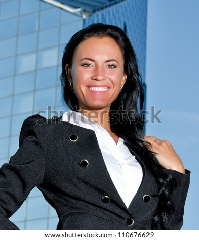 Portrait of pretty woman posing near modern office building