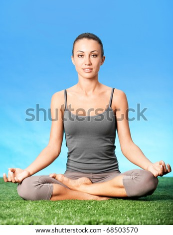 Portrait of pretty woman sitting in pose of lotus - stock photo