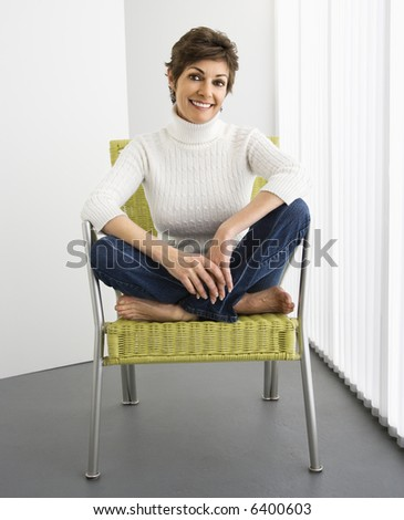 Portrait of pretty woman smiling sitting on modern chair. - stock photo