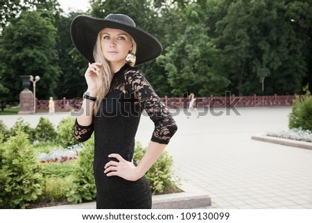 Portrait of pretty woman standing in black hat outdoors - stock photo