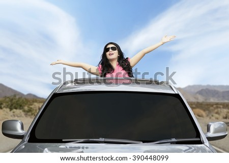 Portrait of pretty woman wearing sunglasses standing in the car and raised hands on the sunroof