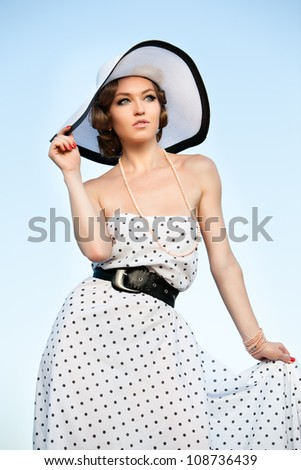 Portrait of pretty woman wearing white dress and straw hat in sunny warm weather day.  Walking at summer park. - stock photo
