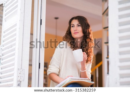 Portrait of pretty woman with a big cup of tea looking through the window