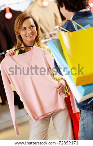 Portrait of pretty woman with new tanktop asking her boyfriend for advice - stock photo