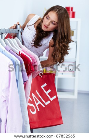 Portrait of pretty woman with red bags in clothing department - stock photo