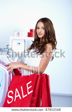 Portrait of pretty woman with red bags looking at camera in clothing department - stock photo
