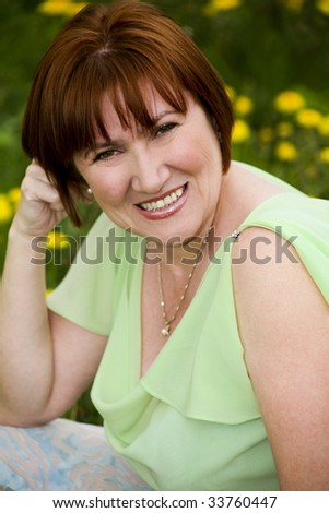 Portrait of pretty woman with smile looking at camera outdoor
